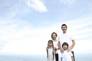 青空を背景に立つ4人家族の写真素材 [FYI03869204]