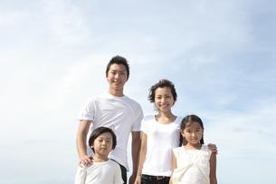青空を背景に立つ4人家族の写真素材 [FYI03869210]