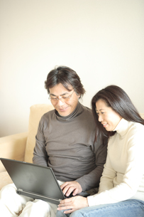 ソファーでパソコンを見る夫婦の写真素材 [FYI03869226]