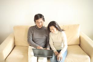 ソファーでパソコンを見る夫婦の写真素材 [FYI03869229]