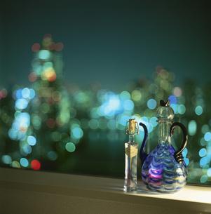 窓辺に置いた水差しと街の灯りの写真素材 [FYI03870170]