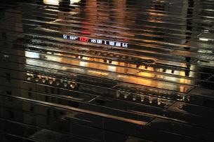 雨のボードウォークに映る夜景の写真素材 [FYI03871391]