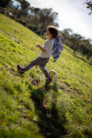 草原を上着を脱いで、走るハーフの幼児の写真素材 [FYI03871394]