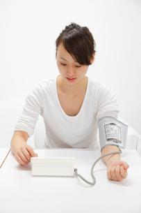 血圧を計る女性の写真素材 [FYI03871840]