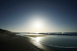 浜辺に寄せる波と朝日の写真素材 [FYI03877461]