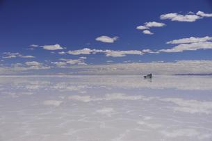 鏡張りのウユニ塩湖と車の写真素材 [FYI03877686]