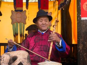 中国 雲南省 束河古鎮 楽器を演奏する男性の写真素材 [FYI03878105]