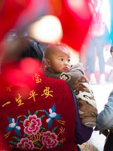 中国 雲南省 三朶節 母に開かれる幼子の写真素材 [FYI03878114]