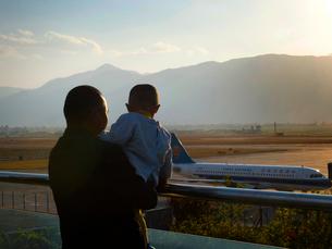中国 雲南省 夕暮れ時の飛行場を眺める親子の写真素材 [FYI03878134]