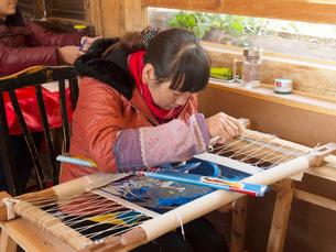 中国 雲南省 刺繍をする女性の写真素材 [FYI03878136]
