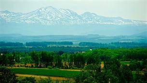 美馬牛小学校と十勝岳連峰の眺めの写真素材 [FYI03878580]