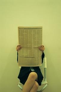 新聞を読む日本人ビジネスウーマンの写真素材 [FYI03879695]