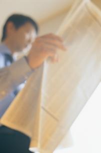 新聞を読む日本人ビジネスマンの写真素材 [FYI03879699]