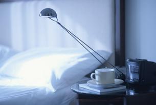 ベッド脇の電気スタンドとカップの写真素材 [FYI03879714]