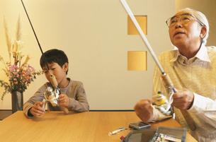 和室で釣り竿を握る老人男性と男の子の写真素材 [FYI03879749]