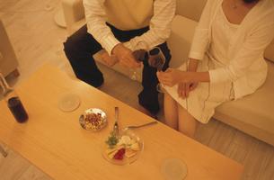 ワインとおつまみのあるリビングのローテーブルと乾杯をする手元の写真素材 [FYI03879785]