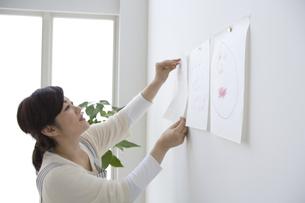 子供の描いた絵を飾る母親の写真素材 [FYI03879885]