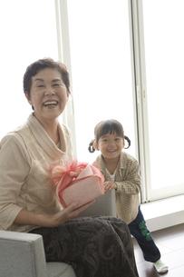 おばあさんにプレゼントを渡す孫の写真素材 [FYI03879899]