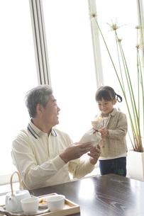 おじいさんにプレゼントを渡す孫の写真素材 [FYI03879900]