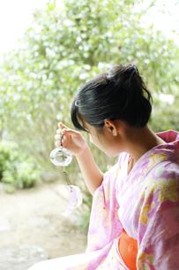 風鈴を持つ浴衣姿の若い女性の写真素材 [FYI03880387]
