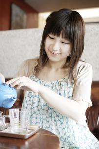 カフェでティ-タイムを楽しむ20代女性の写真素材 [FYI03880403]