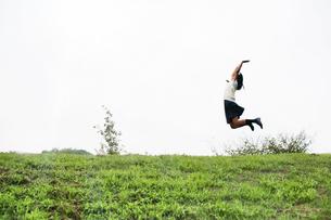 土手でジャンプする制服姿の女子学生の写真素材 [FYI03880419]