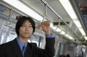 つり革につかまる日本人ビジネスマンの写真素材 [FYI03880762]