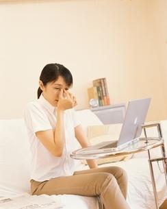 ノートパソコンと目頭を押さえる日本人の女性の写真素材 [FYI03880817]