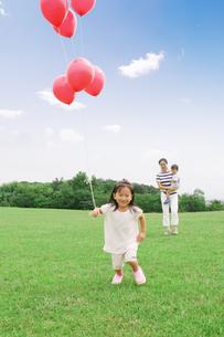赤い風船を持つ女の子と眺める母親の写真素材 [FYI03880920]