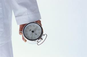 パジャマ姿で目覚し時計を持つ日本人女性の写真素材 [FYI03880957]