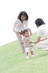 芝生を歩く赤ちゃんと助ける夫婦の写真素材 [FYI03880988]