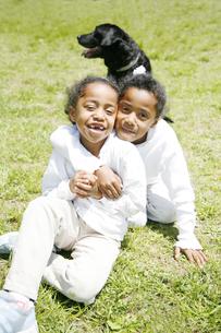 黒人の女の子2人と黒のラブラドールの写真素材 [FYI03881230]