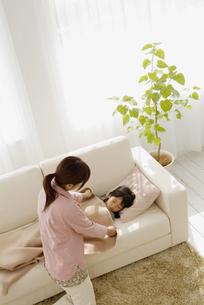 ソファで寝ている娘に毛布をかける母の写真素材 [FYI03881306]