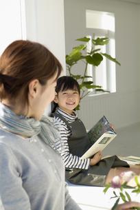 手編みの靴下を持って微笑む妊婦の写真素材 [FYI03881327]