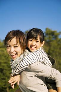 笑顔でおんぶする母と娘の写真素材 [FYI03881344]
