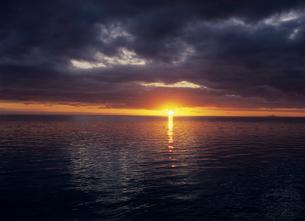 水平線の雲間に落ちる夕日 ボラボラ島の写真素材 [FYI03883693]