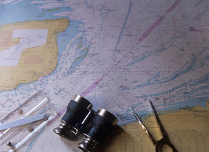 海図と双眼鏡とデバイダーの写真素材 [FYI03884619]