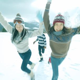 雪原を駆ける3人の若者の写真素材 [FYI03910491]