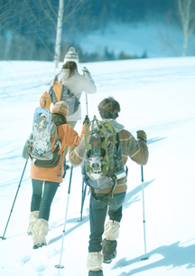 雪原をゆく3人の若者の写真素材 [FYI03910517]