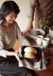 焼きたてのパンを持つ女性の写真素材 [FYI03910742]