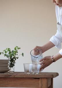 コップに水を注ぐ女性の写真素材 [FYI03910761]