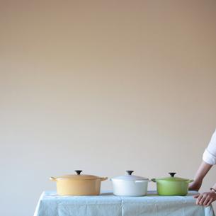 テーブルの上の3つの鍋と女性の手元の写真素材 [FYI03910771]
