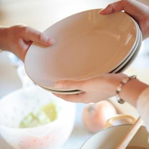 皿を受け取る女性の手元の写真素材 [FYI03910818]