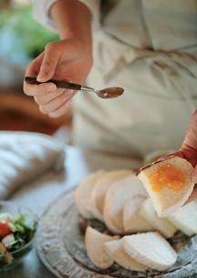 パンにジャムを塗る女性の手元の写真素材 [FYI03910830]