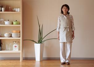 観葉植物の隣に立つ女性の写真素材 [FYI03910833]