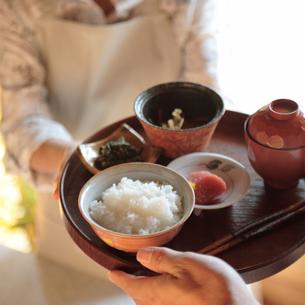 和食を渡す中高年の女性の写真素材 [FYI03910853]