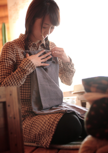 衣服を畳む女性の写真素材 [FYI03911130]