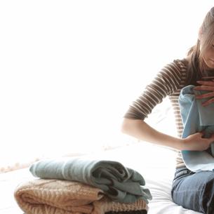 衣服を畳む女性の写真素材 [FYI03911139]