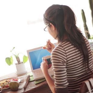 仕事の合間に食事をする女性の写真素材 [FYI03911151]