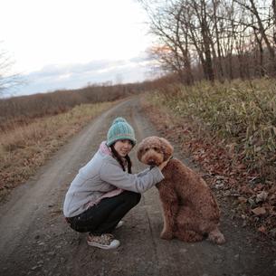 道にしゃがむ女性と犬の写真素材 [FYI03911203]